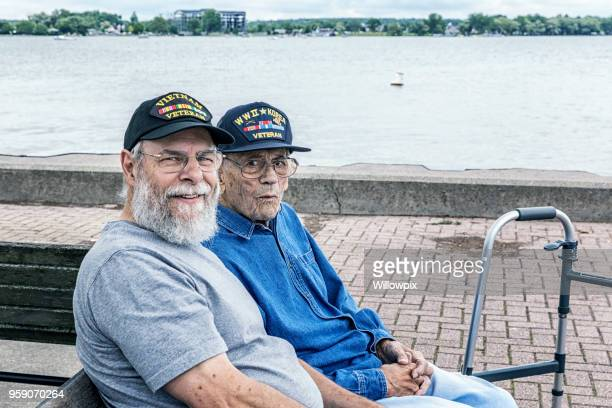 two generations of senior adult usa military veterans sitting at the lake - war veteran stock pictures, royalty-free photos & images