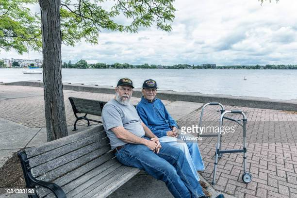 Two Generations of Senior Adult USA Military Veterans Sitting on Park Bench