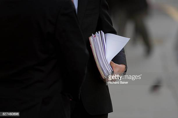 Two gentlemen discuss business in the street in the City of London Standing together to talk we see a detail of the two businessmen one clasping the...