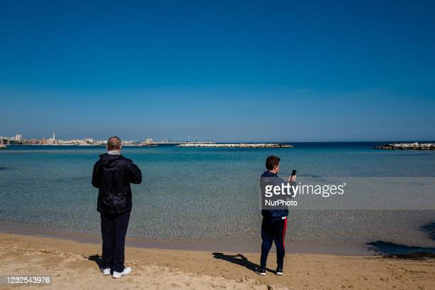 Two gentlemen photograph the beach of Pane e Pomodoro on the first day in the orange zone after more than a month in Bari on April 26, 2021. Italy...