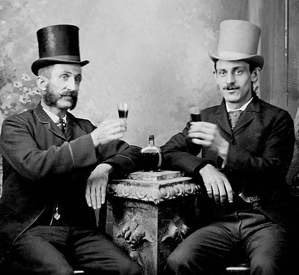 Two gentlemen toast good fortune with a drink, ca. 1885