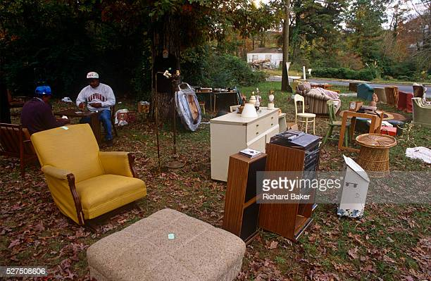 Two Georgian men play cards while waiting for passing trade during an outdoor yard sale in an Atlanta suburb The male friends sit on old chairs at a...