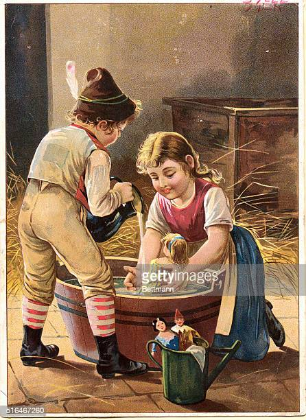 Two German children give a doll a bath in a wooden washtub