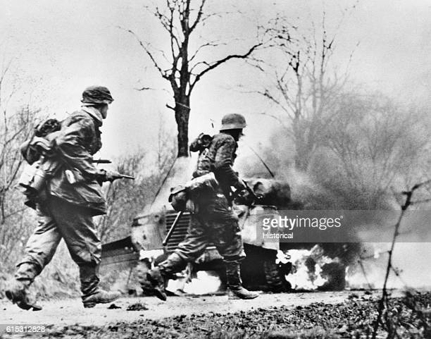 Two German foot soldiers pass by a burning tank during the Battle of the Bulge