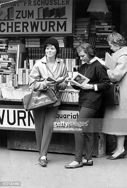 'Two German girls leafing through the books at the book stall nearby the cathedral Heidelberg 1961 '