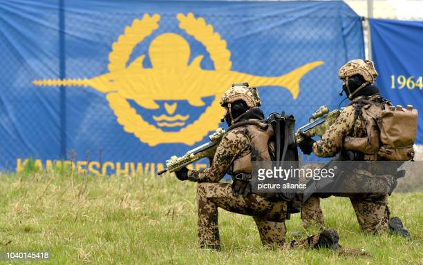 Two German Navy frogmen kneel next to the logo of their fighting unit during a military presentation in Eckernfoerde Germany 5 April 2014 The German...