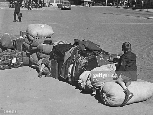 Two German refugee children from the Sovietcontrolled Zone of occupied Germany wait outside Lubeck railway station with their luggage while their...