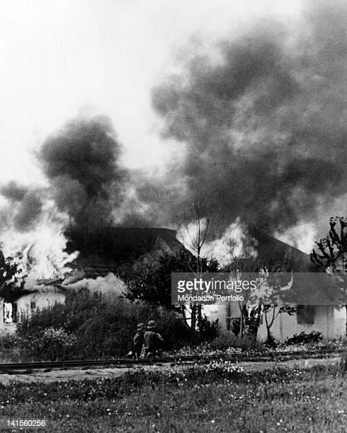 Two German soldiers along a railway ballast watching the houses of a Ukrainian village set on fire by the Russians Ukraine July 1941