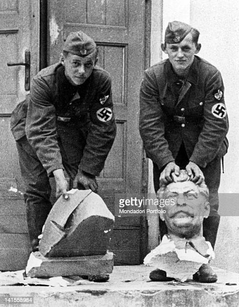 Two German soldiers showing a decapitated bust of Stalin outside a house in Smolensk Smolensk July 1941