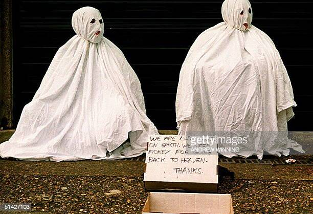 Two ghostly beggars appeal to the sense of humor of passers by in an attempt to relieve them of a little small change on London's Portobello Road 05...