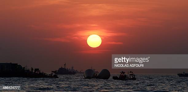 Two giant buoys that mark the spot where the 'Sewol' ferry sank are silhouetted against the sunset in Jindo on April 24 2014 Furious relatives of...