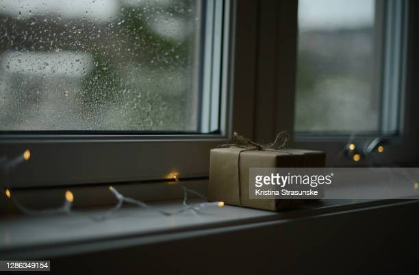 two gift wrapped boxes in a windowsill on a rainy day - kristina strasunske stock pictures, royalty-free photos & images
