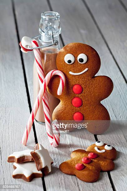 Two gingerbread men, bottle of cocoa, sugar canes and cinnamon stars on grey wood