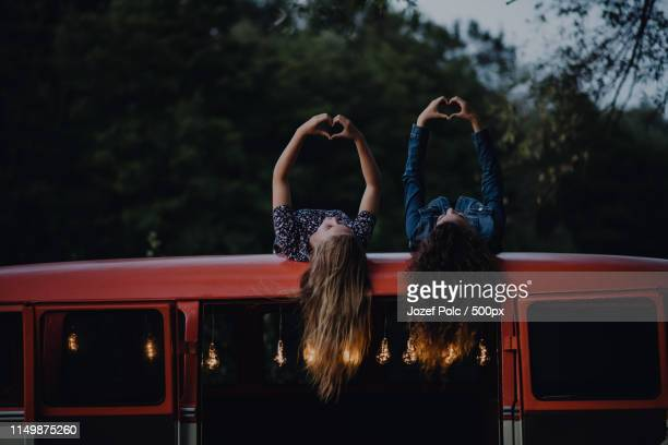 two girl friends at dusk outdoors on a roadtrip through countryside, having fun - female friendship stock pictures, royalty-free photos & images