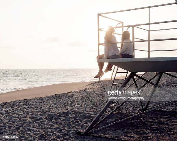 Two girl friends hanging out on life guard tower