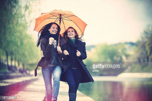 Two girl friends laughing, arms around each other and walking