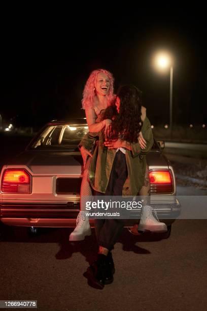 deux amis de fille se penchant sur la voiture ayant l'amusement la nuit - ados lesbiennes en couple photos et images de collection