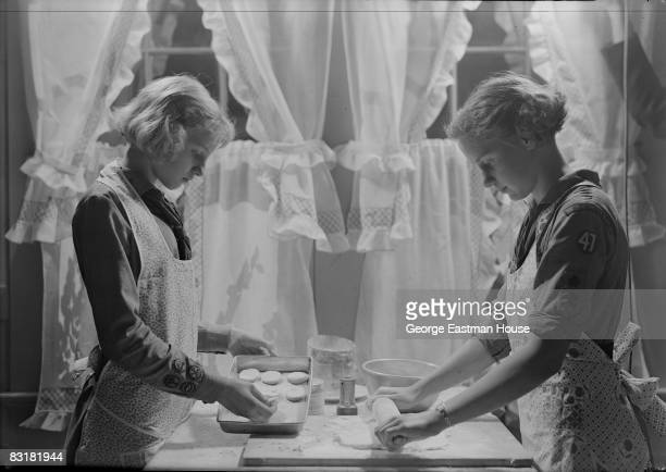 Two girl scouts making cookies One rolls the dough while the other sets the cookies on a tray United States ca1920s