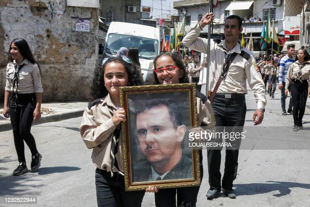 Two girl scouts walk with a portrait of Syria's President Bashar al-Assad as they march during an Orthodox Palm Sunday procession in the Dwelaa...