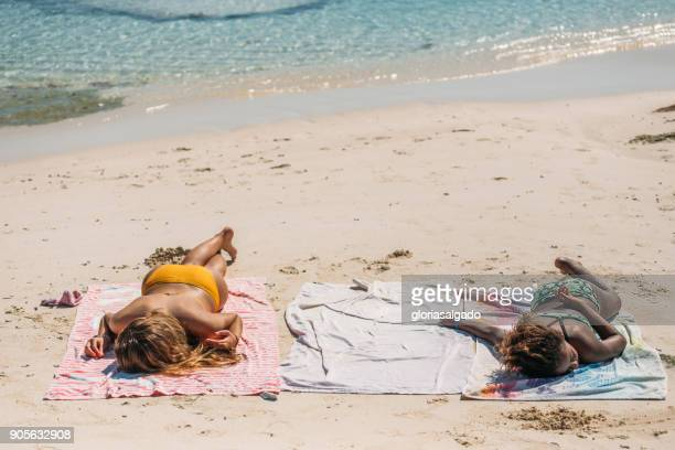 two girl sunbathing on the beach - girls sunbathing stock photos and pictures