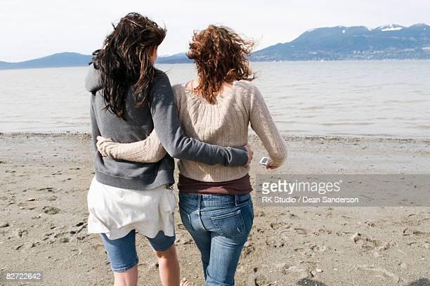 two girl walking towards water on beach - amigos abrazados espaldas fotografías e imágenes de stock