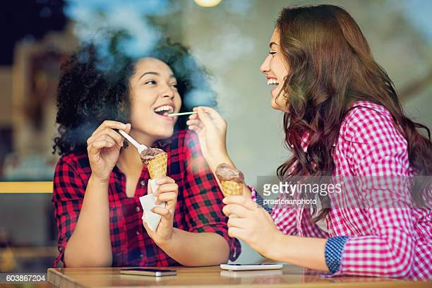 Two girlfriends are eating ice cream