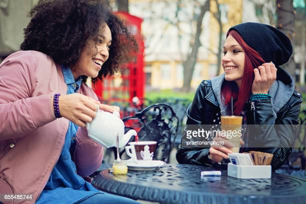 two girlfriends are having fun in cafeteria - english teapot stock pictures, royalty-free photos & images