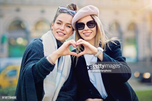 Two girlfriends are making heart with their hands on the street