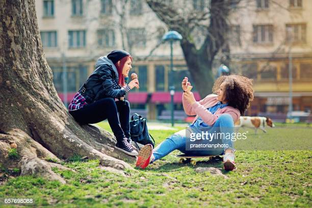 Two girlfriends are sitting in the park and taking pictures