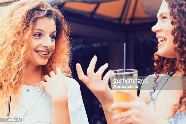 Two girlfriends chatting and drinking orange juice