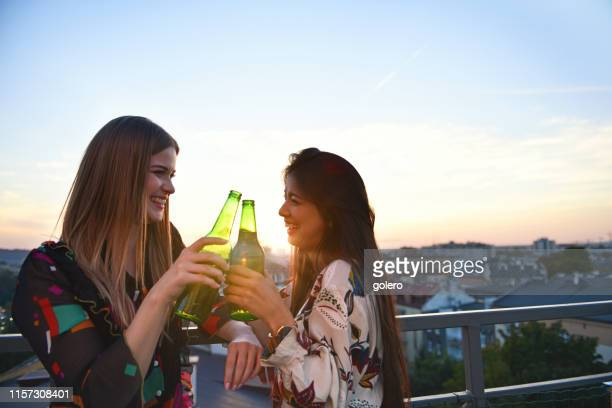 two girlfriends drinking beer outdoors - golden hour stock pictures, royalty-free photos & images