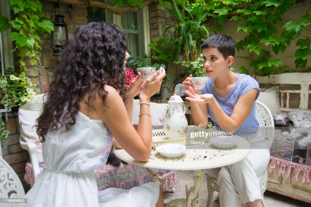 Two Girlfriends Drinking Tea And Talking In The Patio High-Res Stock Photo  - Getty Images
