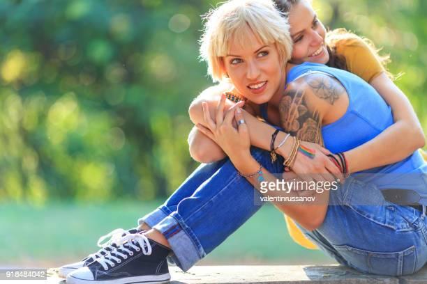 Zwei Freundinnen umarmen im park