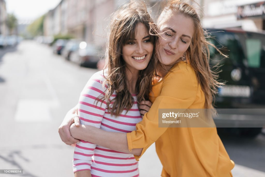 Two girlfriends embracing in the city : Stockfoto