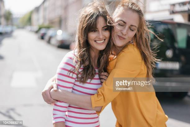 two girlfriends embracing in the city - ermutigung stock-fotos und bilder