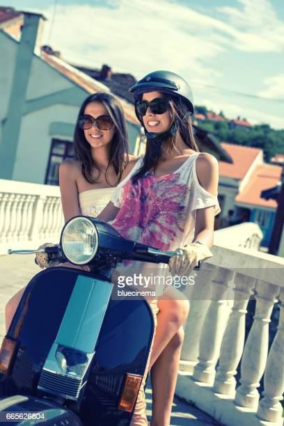 two girlfriends enjoying a summer's day - moped stock photos and pictures