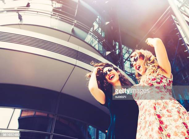two girlfriends have fun in town - potsdamer platz stock pictures, royalty-free photos & images