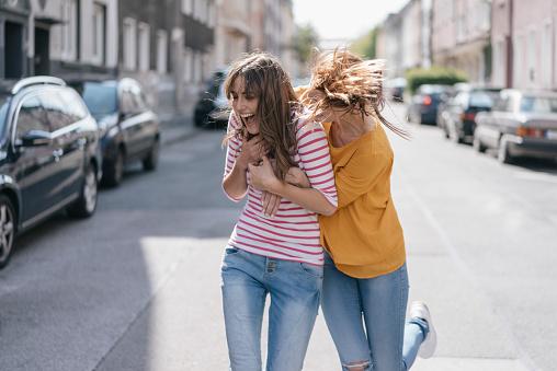 Two girlfriends having fun in the city, running - gettyimageskorea