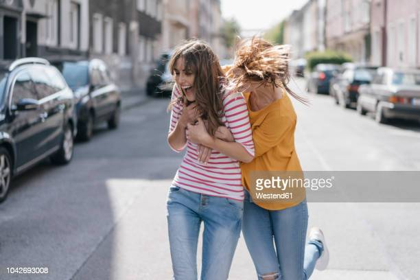 two girlfriends having fun in the city, running - lachen stock-fotos und bilder