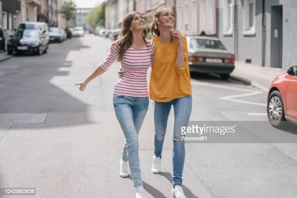 two girlfriends having fun in the city, walking arm in arm - weibliche freundschaft stock-fotos und bilder