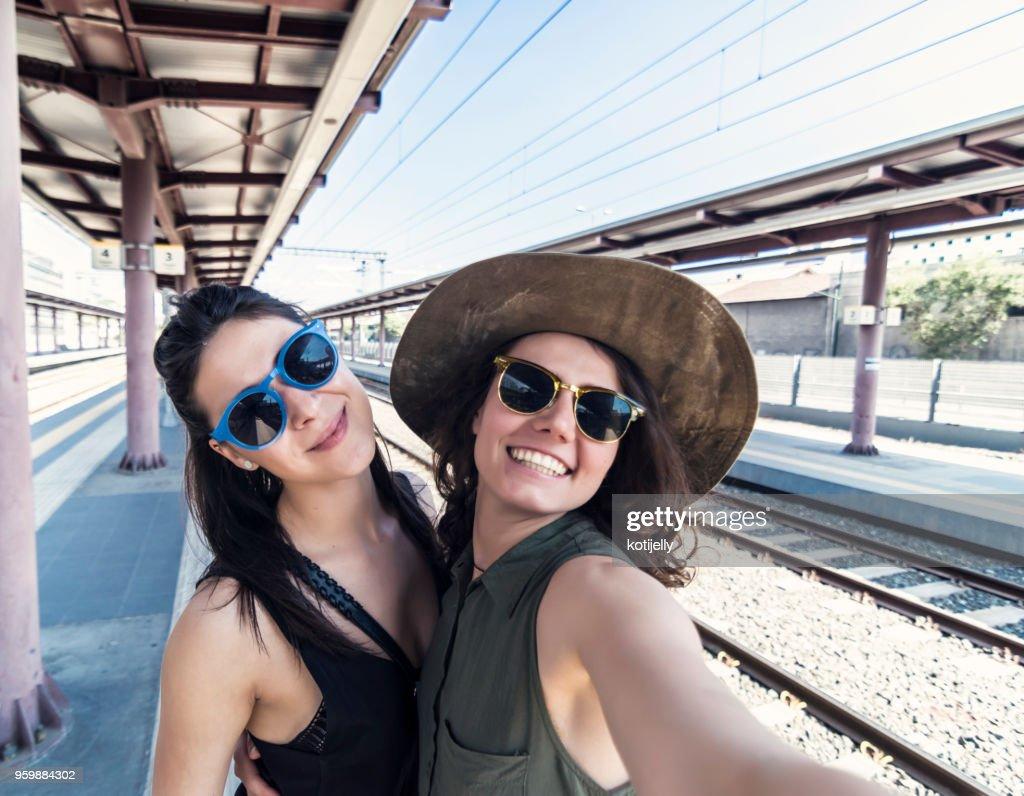 Two girlfriends in a train station : Foto stock