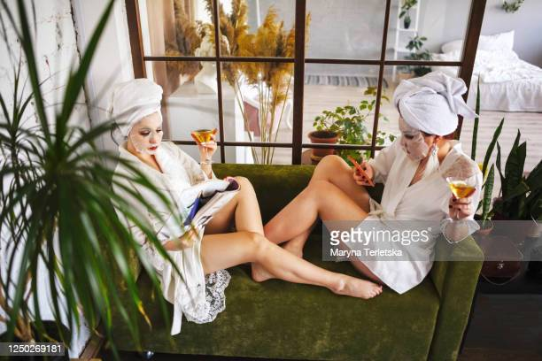 two girlfriends in bathrobes and face masks are sitting on the couch. - petite amie photos et images de collection
