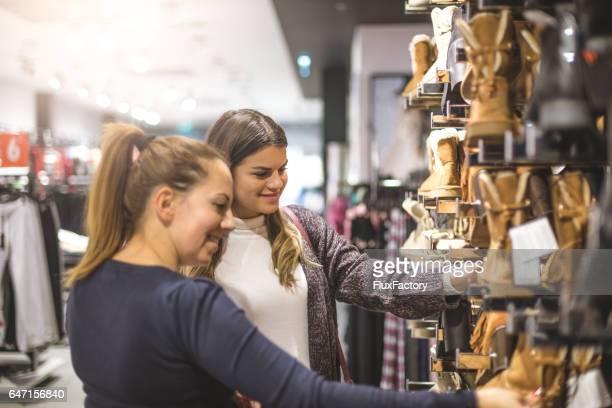 Zwei Freundinnen im Store kaufen Stiefel