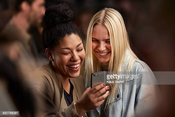 Two girlfriends looking at smartphone together