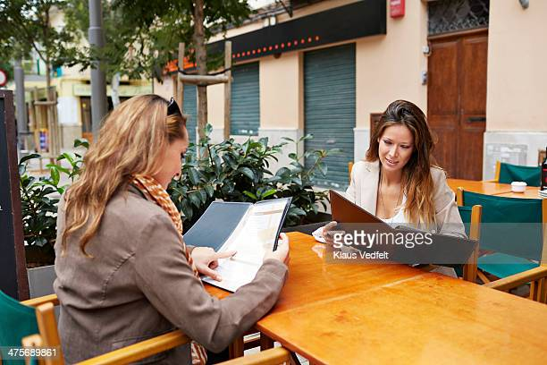 two girlfriends looking at the menu at café - klaus vedfelt mallorca stock pictures, royalty-free photos & images