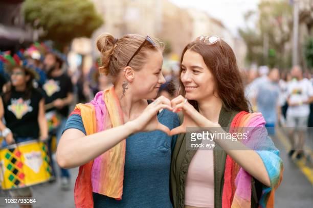 deux copines faire des coeur avec leurs mains dans la rue - ados lesbiennes en couple photos et images de collection