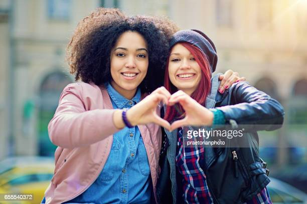Two girlfriends making heart with their hands on the street