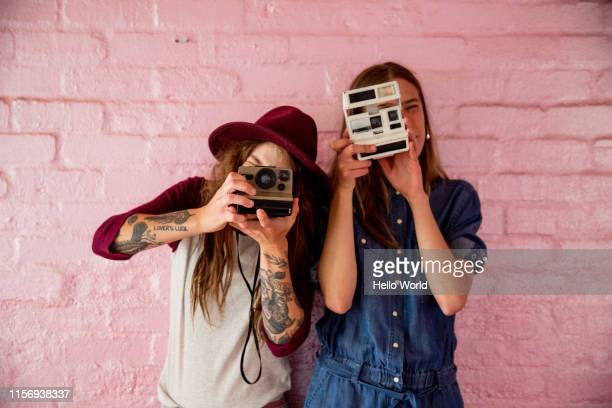 two girlfriends on pink wall backdrop snapping with retro cameras - fotosessie stockfoto's en -beelden