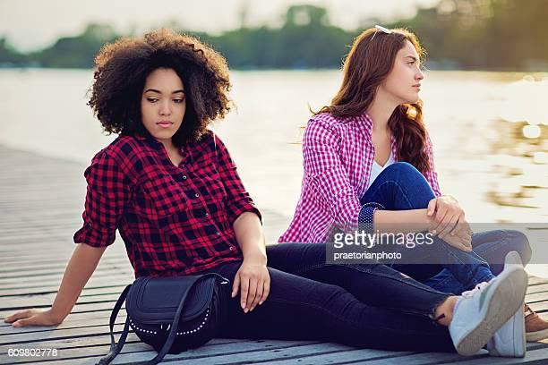 two girlfriends on the lake with relationship difficulties - furioso fotografías e imágenes de stock