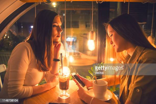 two girlfriends sitting in the coffee shop - ignoring stock pictures, royalty-free photos & images